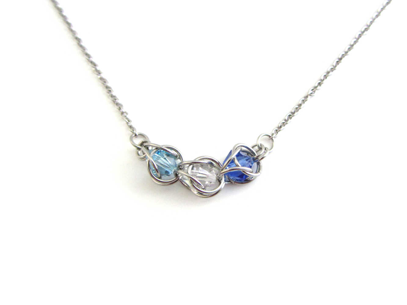 catpured light blue, clear and dark blue crystal beads chainmaille section on a stainless steel chain