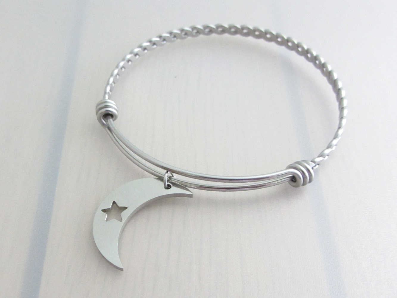 stainless steel crescent moon charm with cut out star on a bangle with braided twist pattern