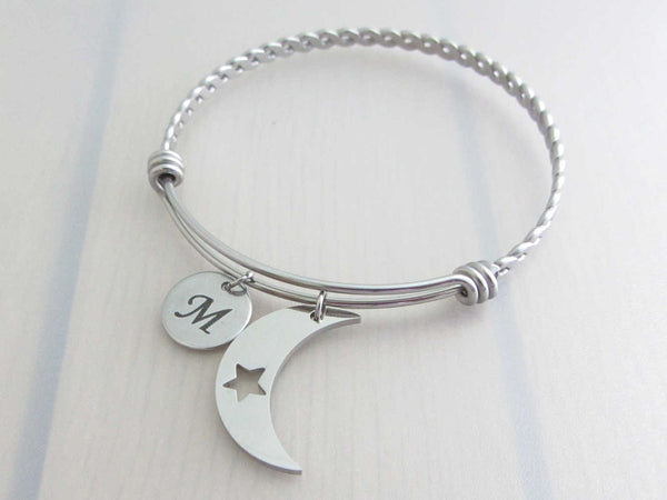 stainless steel laser engraved capital initial letter disc charm and crescent moon with cut out star charm on a bangle with braided twist pattern