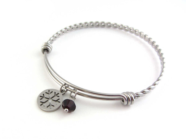 stainless steel snowflake charm and a red crystal charm on a bangle with braided twist pattern