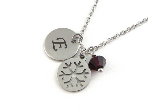 laser engraved capital initial letter disc charm, snowflake charm and a red crystal charm on a stainless steel chain
