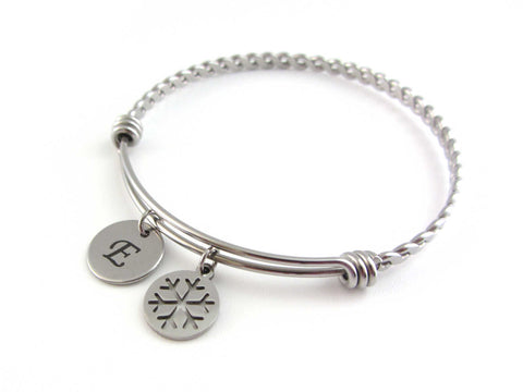 stainless steel laser engraved capital initial letter disc charm and snowflake charm on a bangle with braided twist pattern