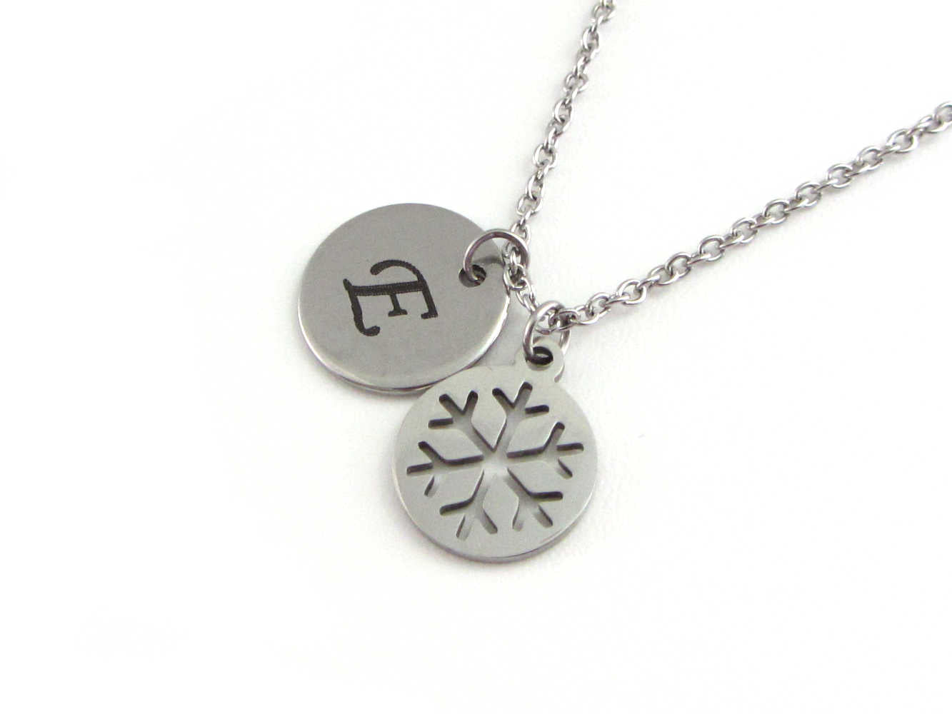 laser engraved capital initial letter disc charm and snowflake charm on a stainless steel chain