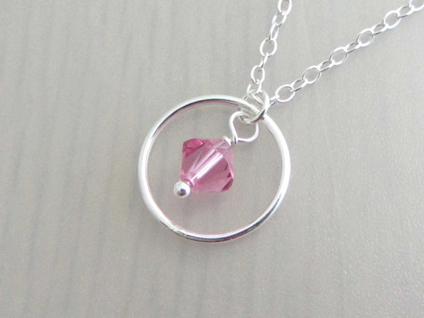 silver circle ring and pink coloured crystal charm on a silver chain