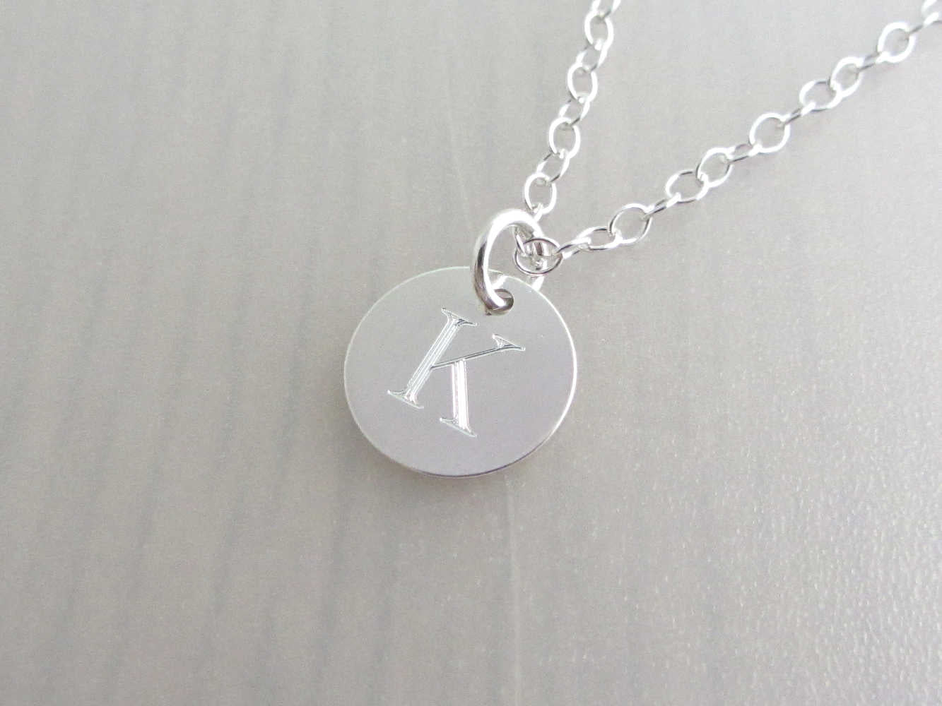 silver engraved capital initial letter disc charm on a silver chain