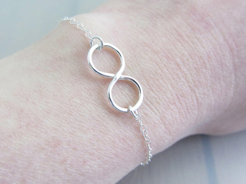 silver infinity charm on a silver chain bracelet on wrist