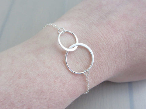 two linked silver circle rings on a silver chain bracelet on wrist