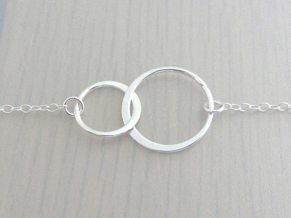 two linked silver circle rings on a silver chain