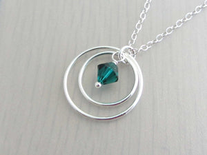 two silver circle rings and green coloured crystal charm on a silver chain