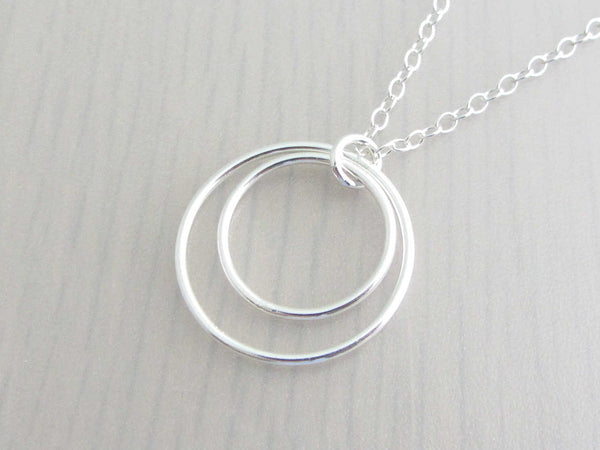 two silver circle rings on a silver chain