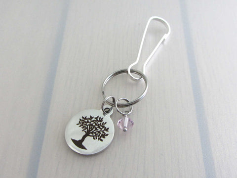 laser engraved tree charm and a pale purple crystal charm on a bag charm