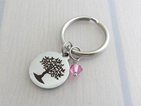 laser engraved tree charm and a pink crystal charm on a keyring