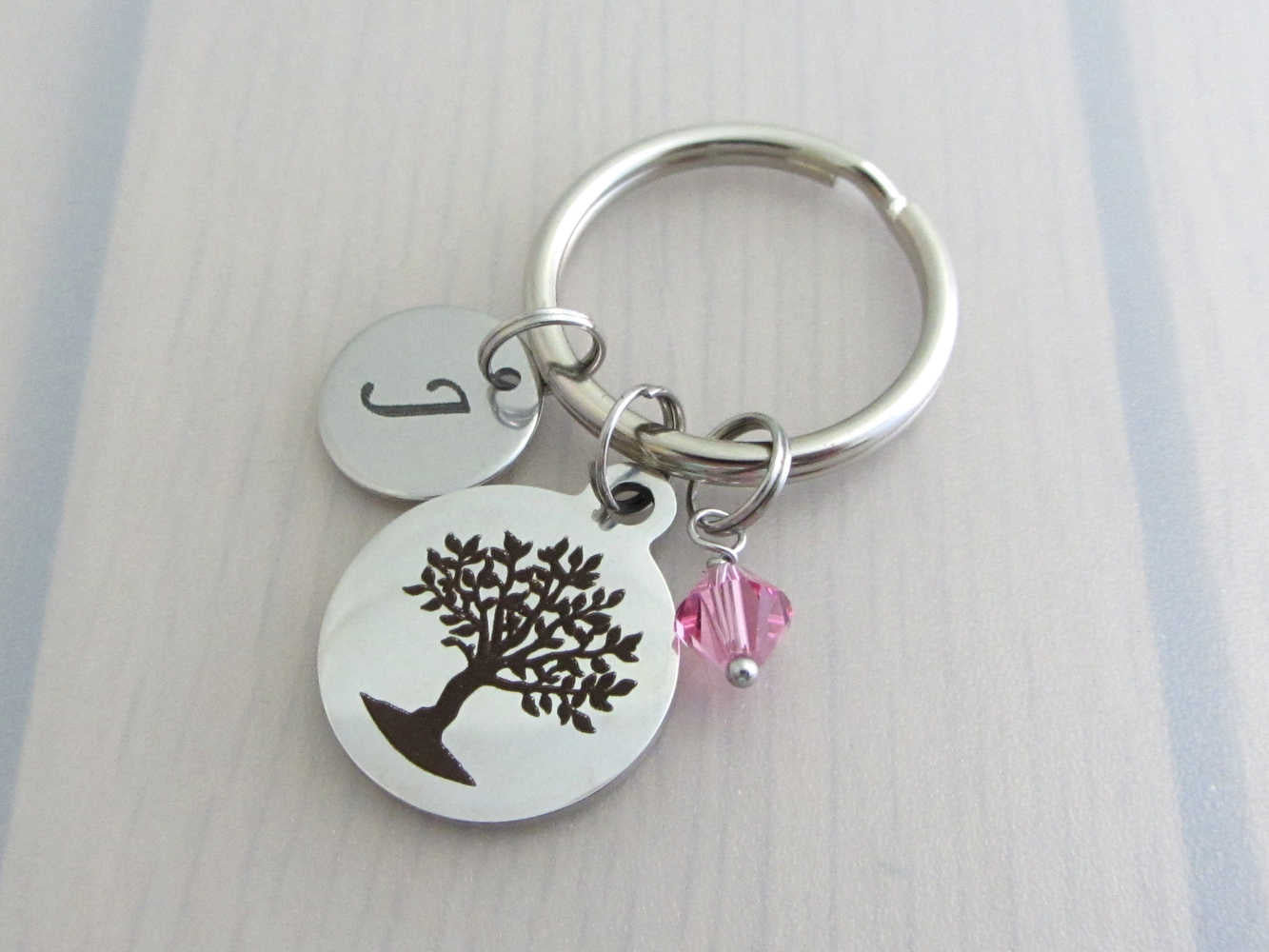 laser engraved capital initial letter disc charm, laser engraved tree charm and a pink crystal charm on a keyring