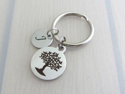 laser engraved capital initial letter disc charm and a laser engraved tree charm on a keyring