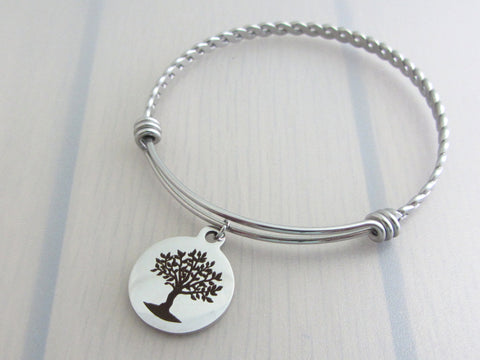 stainless steel laser engraved tree charm on a bangle with braided twist pattern