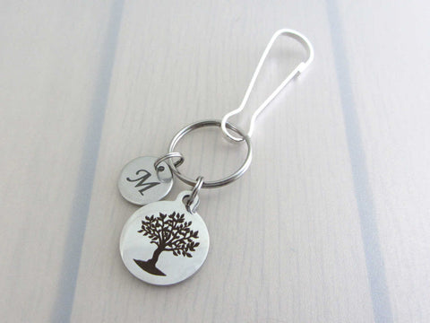laser engraved capital initial letter disc charm and a laser engraved tree charm on a bag charm