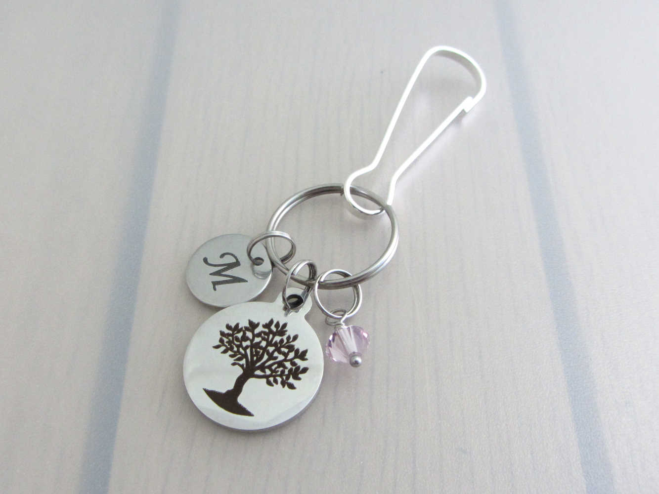 laser engraved capital initial letter disc charm, laser engraved tree charm and a pale purple crystal charm on a bag charm