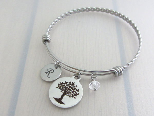 laser engraved capital initial letter disc charm, laser engraved tree charm and a clear crystal charm on a bangle with braided twist pattern