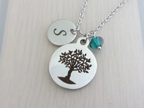 laser engraved capital initial letter disc charm, laser engraved tree charm and a green crystal charm on a stainless steel chain