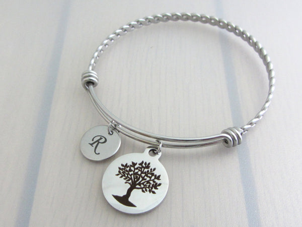 stainless steel laser engraved capital initial letter disc charm and laser engraved tree charm on a bangle with braided twist pattern