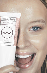 Girl holding up body balm tube over eye