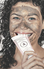 Girl with creamy face scrub on face and biting tube
