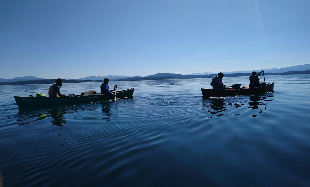 Two canoes on a serene lake. Two people sit in each canoe.