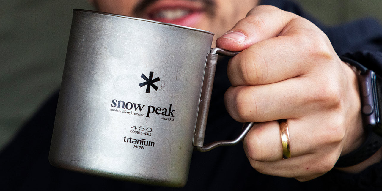 A person holding a Snow Peak titanium mug with the logo engraved on the front