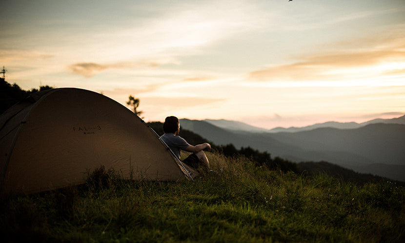 Person sitting in front of their tent overlooking a beautiful vista.