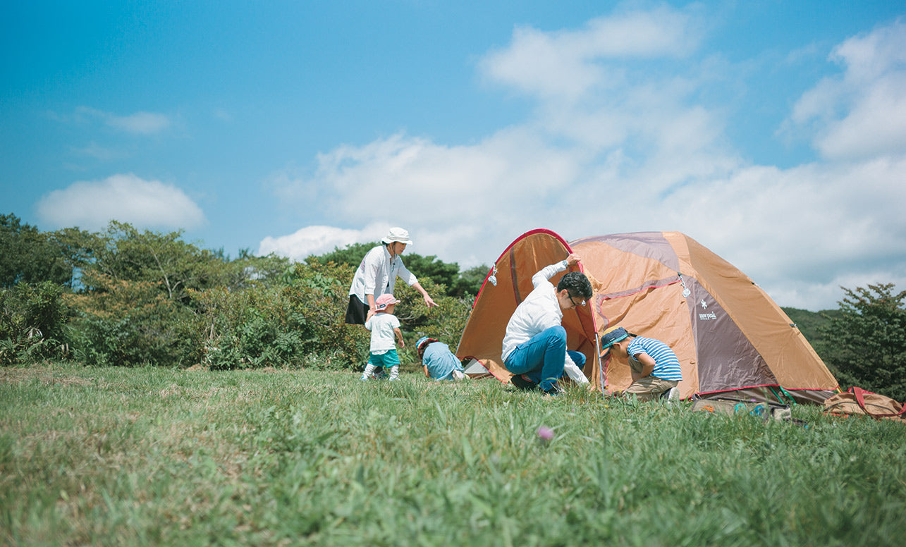 Image of a family setting up a tent in a large campfield under a blue sky.
