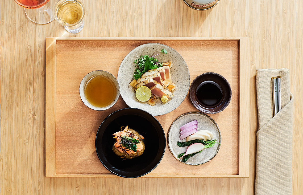 A beautiful wood tray filled with small plates of perfectly plated food.
