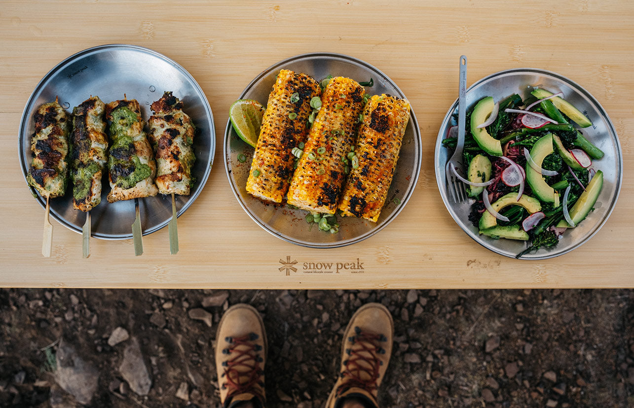 Image of the grilled chicken skewers, corn, and grain salad plated side by side.