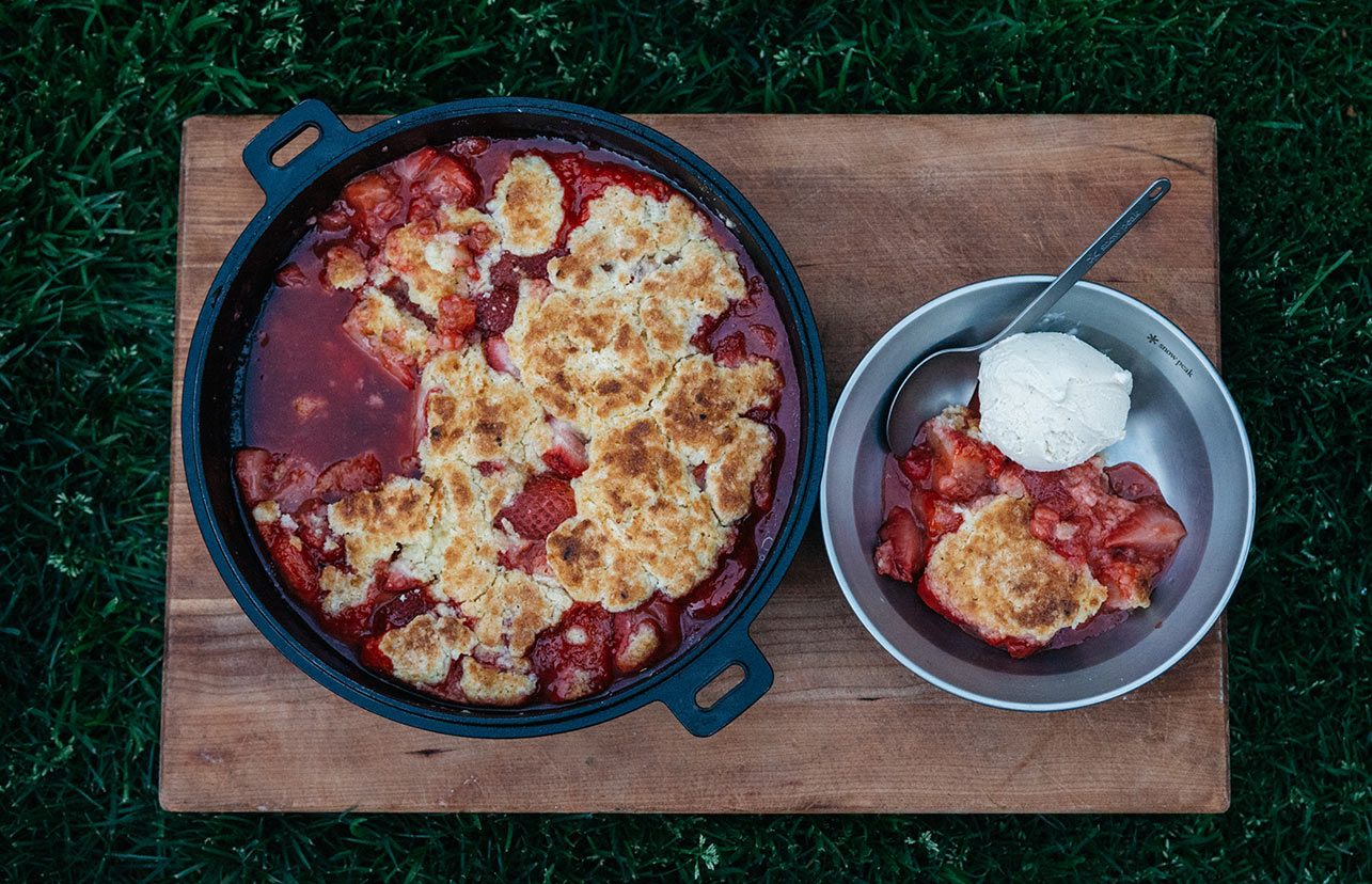 Strawberry Buttermilk Biscuit Cobbler in a cast iron pan with a serving plated into a bowl sitting next to it.