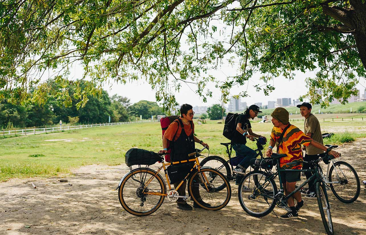 A group of four bike riders prepare to go on a ride in a park. Gear is stored on each of their bikes.