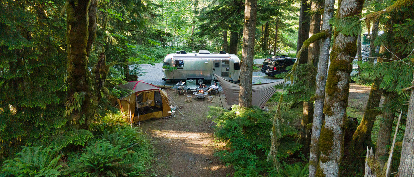 Image of a camp setup with a vintage Airstream, Snow Peak shelter and tarp, and a campfire nestled into the woods of the Pacific Northwest.
