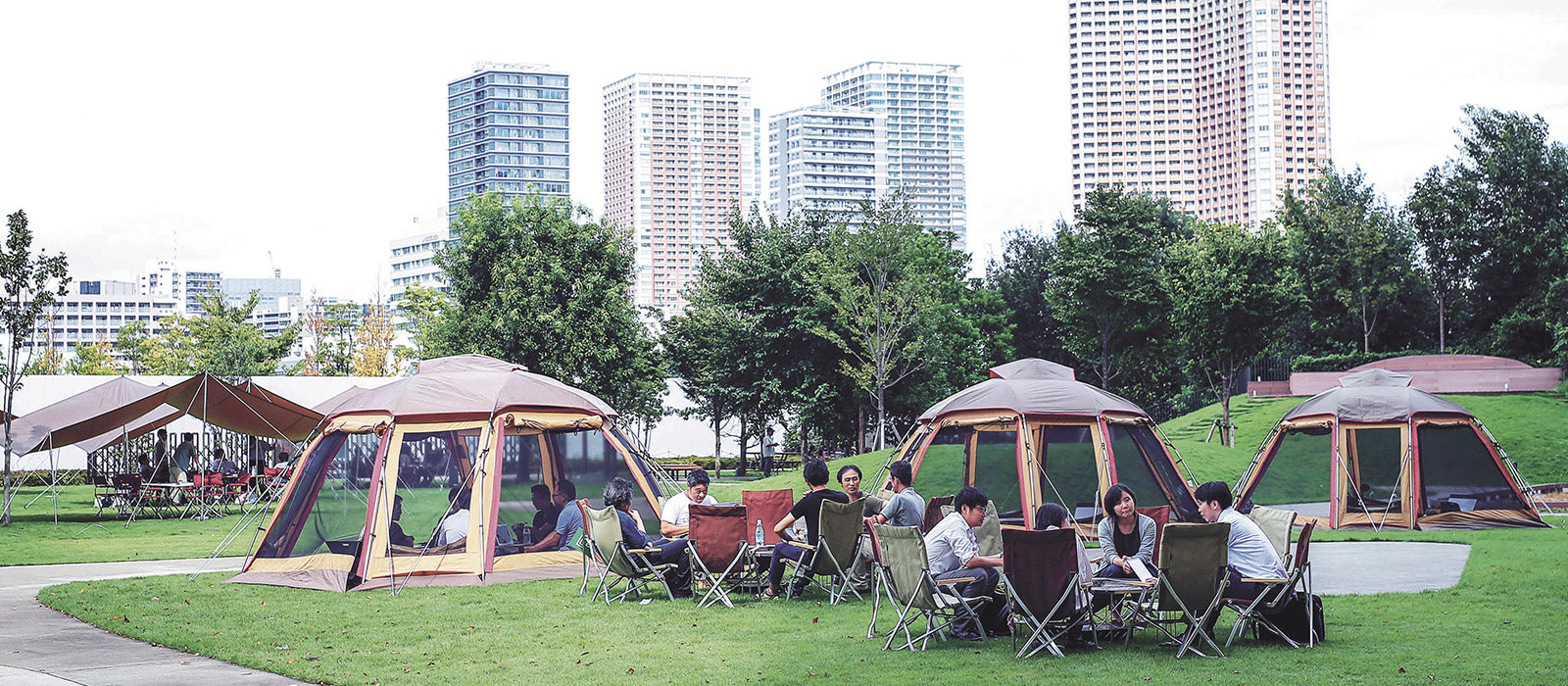 Image of campers on a campfield in front of urban setting