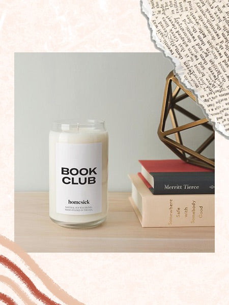 Image of the Homesick Book Club Candle accompanied by a stack of books and decor.