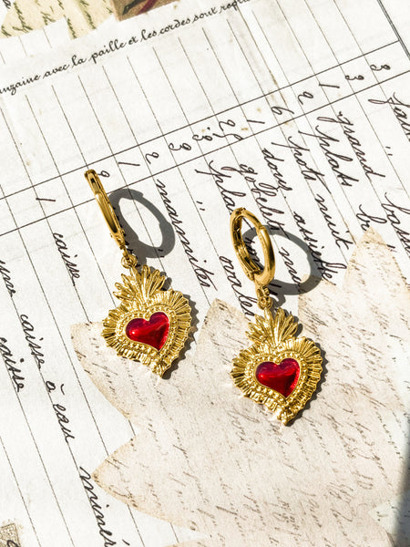 Gold Fortune & Frame Sacred Heart with red ruby enamel Earrings with a script font paper background.