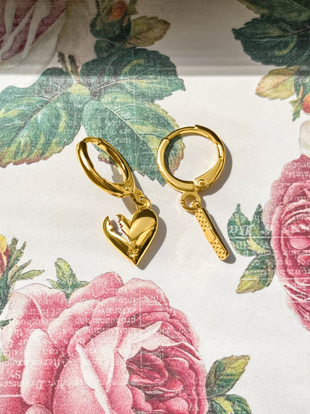 Gold Fortune & Frame Mismatched Mending Heart + Bandaid Earrings on a floral paper background.