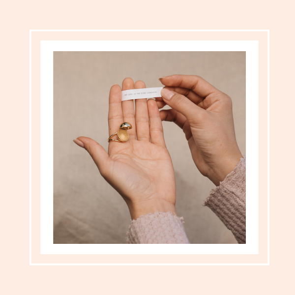 Hands holding our Sphere Secret Ring with a daily affirmation quote.