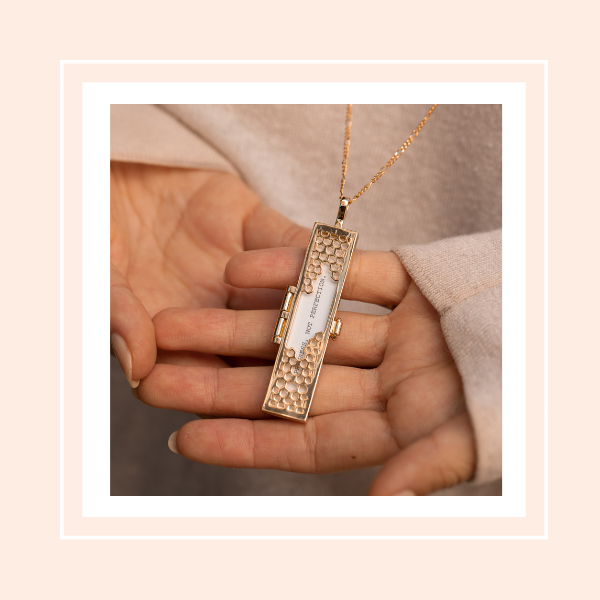 Hands holding Honeycomb Fortune Locket with a daily affirmation quote.