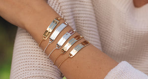 Shown here: five of our engraved bar bracelets, worn as layers, on a model's arm.
