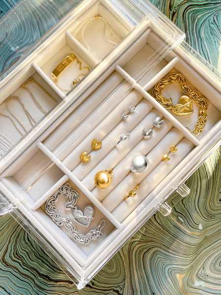 Organizing and storing Fortune & Frame rings, necklaces, and bracelets in a clear jewelry box.