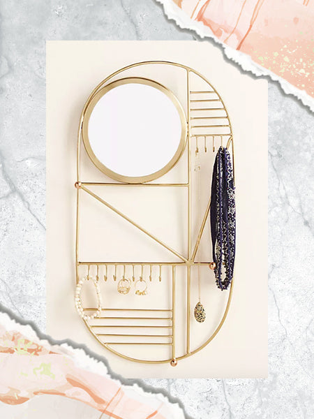 A gold jewelry wall organizer with a mirror serves as both a piece of decor and a jewelry storage solution.