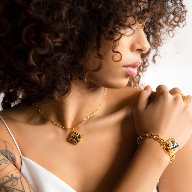 Image shows a model wearing a black book locket necklace and a book bracelet.