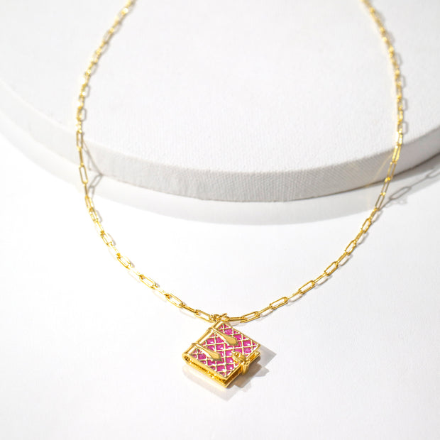 Image shows a magenta book locket necklace on a white background.