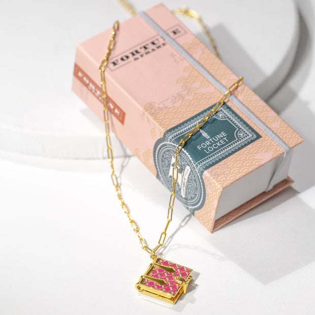 Shown here is a magenta book locket necklace placed on the fortune and frame story book packaging.