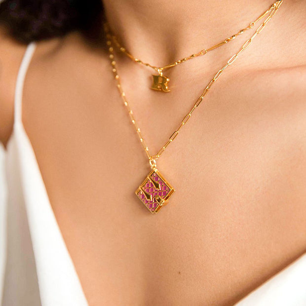 Image shows a model wearing the magenta book locket and an 'R' initial necklace layered.