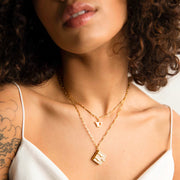 Image shows a model wearing the pearl book locket paired with a 'V' initial necklace.