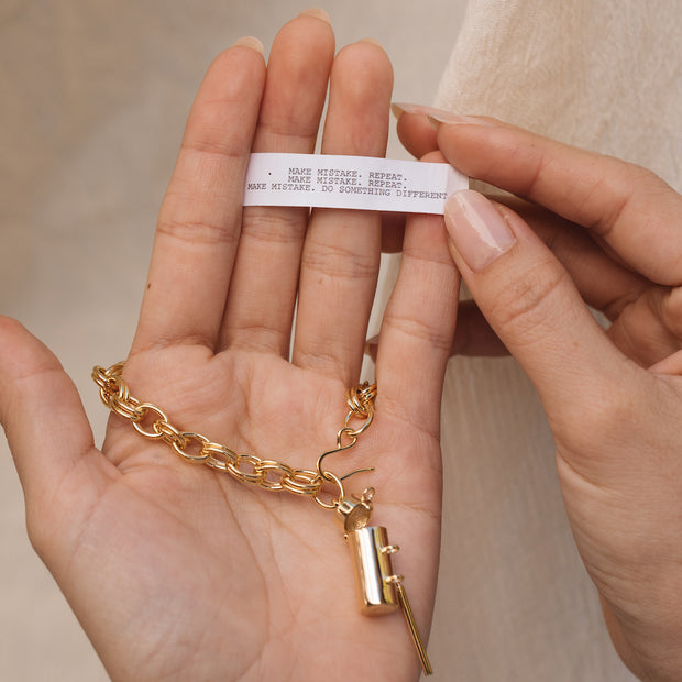 Image shows a model holding a capsule wand bracelet and a  fortune that reads 'Make Mistake. Repeat. Make Mistake. Repeat. Make Mistake. Do Something Different.'